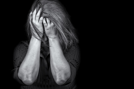 Black and white image of a young woman crying useful to illustrate stress, depression or domestic violence Stock Photo