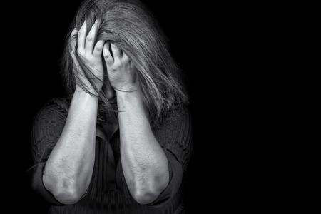 violencia intrafamiliar: Imagen en blanco y negro de una mujer joven llorando útil para ilustrar el estrés, la depresión o la violencia doméstica Foto de archivo