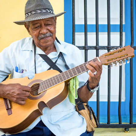 guitar player: Street musician playing traditional cuban music on an acoustic guitar for the entertainment of tourists in a typical colorful Old Havana street