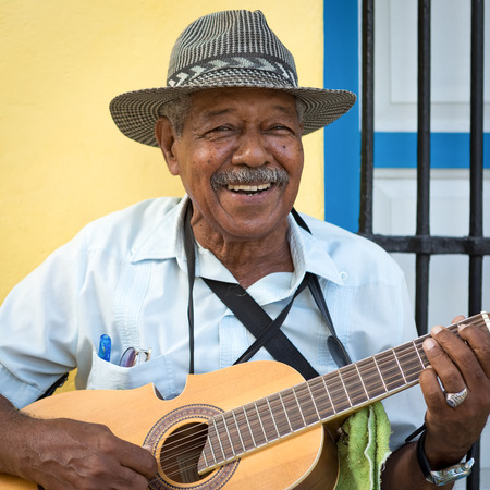 Street musician playing traditional cuban music on an acoustic guitar for the entertainment of tourists in a typical colorful Old Havana street