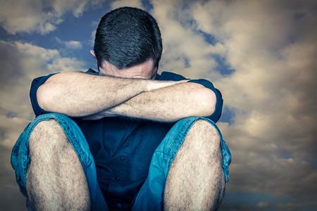 Smutný mladý muž skrýval tvář a plakala s bouřlivé mraky na pozadí Reklamní fotografie