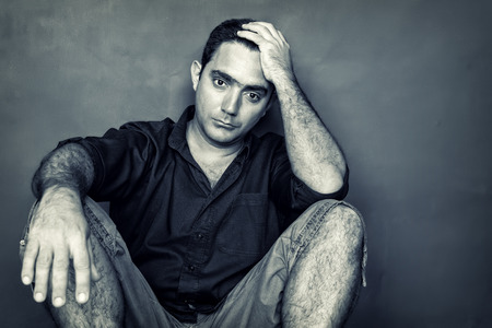 Grunge desaturated  image of a stressed and worried young man sitting on the floor isolated on a black background photo