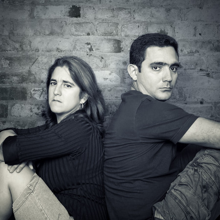 Divorce,problems - Young couple angry at each other sitting back to back with a bricks wall background photo