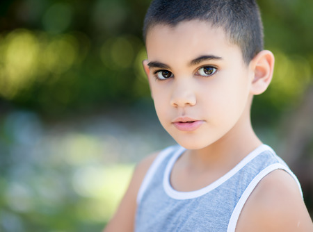 diffused: Portrait of a latin child with a diffused green vegetation background