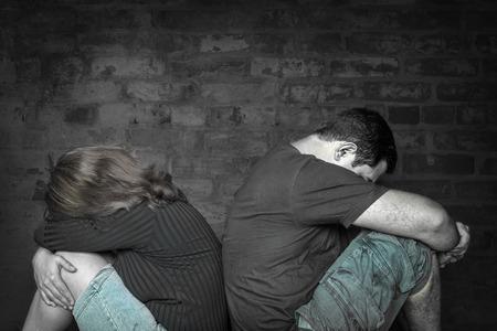 divorcio: Divorcio, problemas - Pareja joven enojados el uno al otro sentados espalda con espalda con un fondo de pared de ladrillos