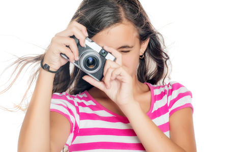 viewfinder vintage: Beautiful young girl taking a picture with a vintage looking compact camera looking through the viewfinder  isolated on white
