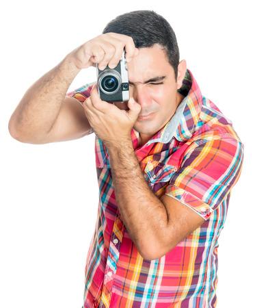 amateur: Hombre hispánico que usa una cámara compacta en busca de cosecha aislado en blanco Foto de archivo