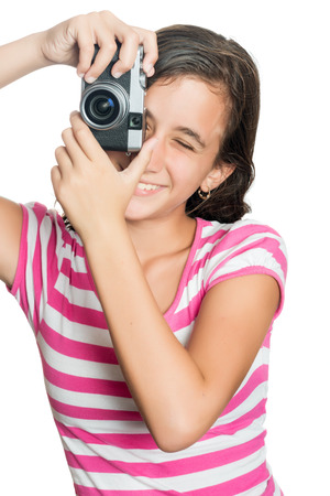 viewfinder vintage: Fun happy young girl taking a photo with a vintage looking compact camera looking through the viewfinder  isolated on white