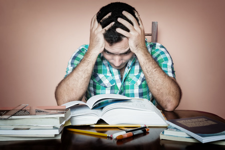 examination stress: Grunge image of a stressed overworked man studying Stock Photo