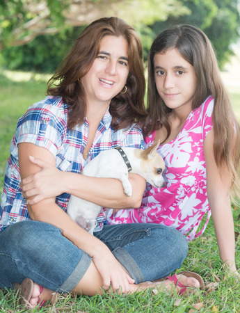 Young hispanic woman, her teenage daughter and their small chihuahua dog at a park photo