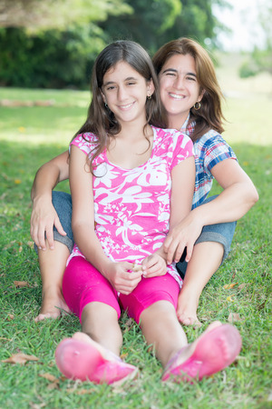 Hispanic teenage girl and her mother sitting in the grass at a beautiful park photo