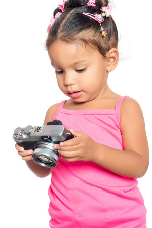 Multiracial small girl holding a compact camera isolated on white photo