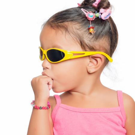 Multiracial small girl  wearing bright  yellow sunglasses isolated on white photo