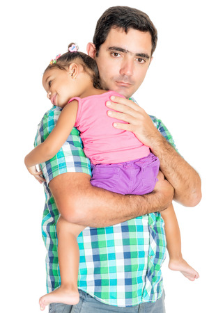 Serious hispanic father carrying his tired small daughter isolated on white photo