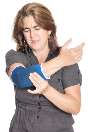 Woman with an injured painful arm elbow wearing a therapeutic elastic support band isolated on white Stock Photo