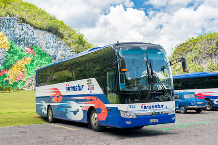 Tour bus at the Mural of Prehistory in the Vinales Valley in Cuba, a famous touristic landmark worldwide known for its unique natural beauty