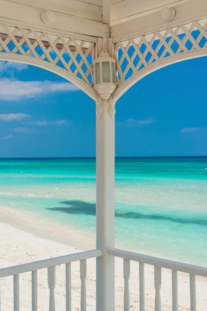 View of Varadero beach in Cuba framed by the columns of a beautiful wooden terrace photo