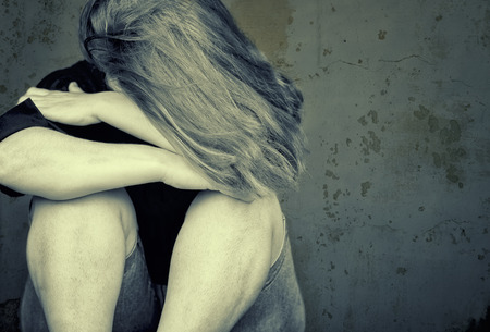 abuse young woman: Young woman crying sitting on the floor  Stock Photo