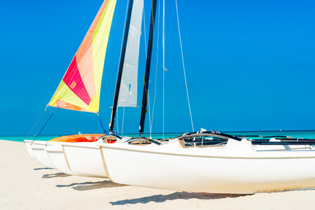 Group of catamarans with colorful sails on a tropical beach in Cuba photo