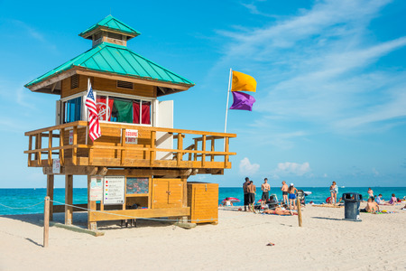 People enjoying the beach near an iconic lifeguard tower in South Beach on a beautiful summer day