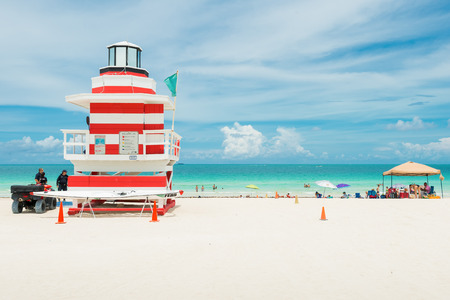 People enjoying the beach next to a colorful lifeguard tower in Miami Beach