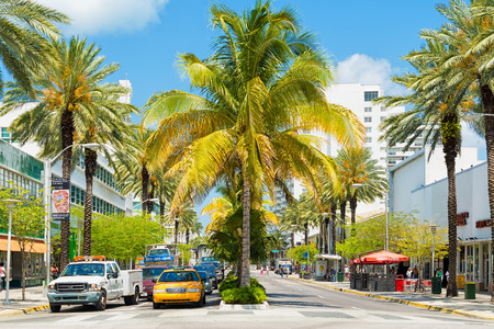 Traffic and shops among tropical palm trees at Lincoln Road, a famous tourist landmark at Miami Beach