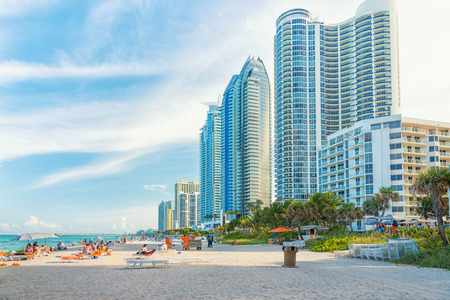 Tourists and locals enjoying the beach at Miami with a view of the skyscrapers next to the shore