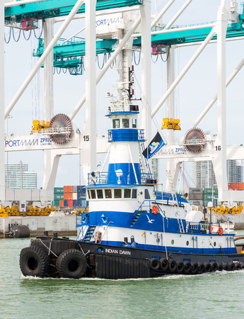 Tugboat sailing in the Port of Miami with containers and cranes on the background