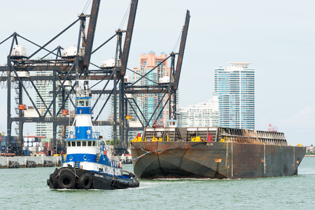 Tugboat pulling a barge in the Port of Miami with containers and cranes on the background