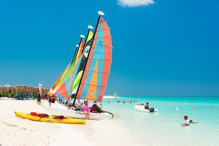 CAYO SANTA MARIA, CUBA - JULY 16, 2014 : Tourists enjoy the beautiful beach with colorful sailboats