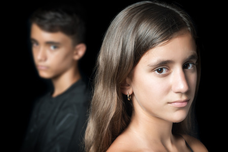 Teenage couple sad and angry at each other on a black background