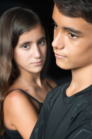 Sad teenagers - boy and girl - isolated on a black background
