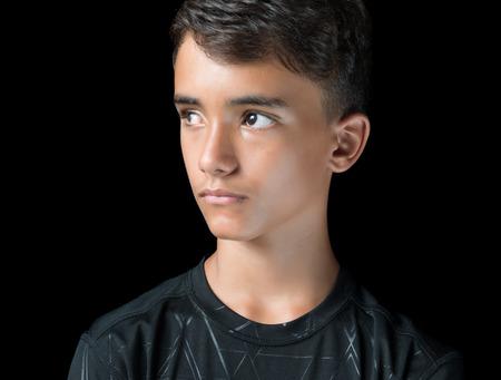 Portret van een ernstige Spaanse tiener geïsoleerd op zwart