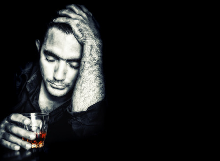 Emotional portrait of a drunk man holding a glass of whisky on a black