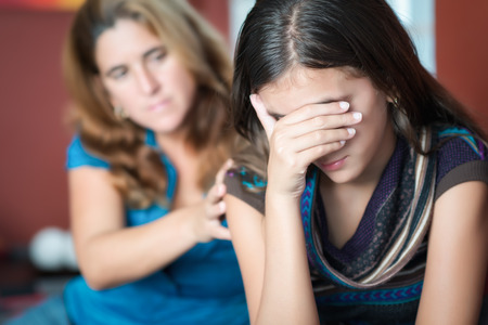 cries: Teenager problems - Mother comforts her troubled teenage daughter who cries Stock Photo