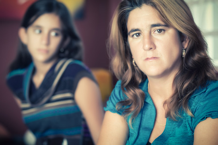 rebellious: Teenager problems - Sad and worried mother with her rebellious teenage daughter on the background