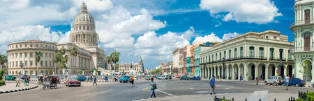 Street scene with people and old cars next to the Capitol buildiing in Old Havana