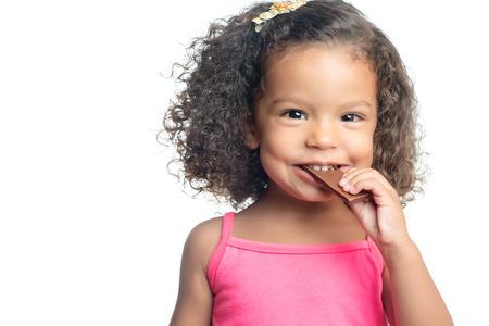 Blij meisje met een afro kapsel het eten van een reep chocolade op wit wordt geïsoleerd Stockfoto