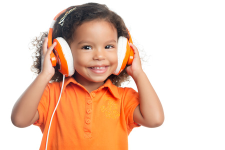 mixed race baby: Lttle girl with an afro hairstyle enjoying her music on bright orange headphones (isolated on white)