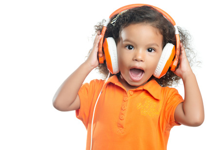 Excited little girl with an afro hairstyle enjoying her music on bright orange headphones (isolated on white) photo