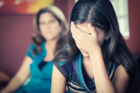 cries: Teenager problems - Teenage girl cries while her mother looks at her on the background