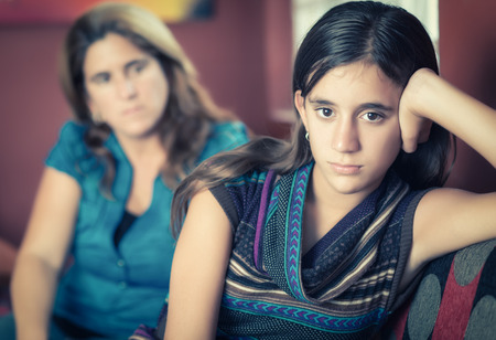 rebellious: Teenager problems - Defiant teenage girl after a fight with her worried mother looking at her Stock Photo