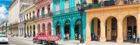 Street scene with people, old cars and colorful buildings in Old Havana