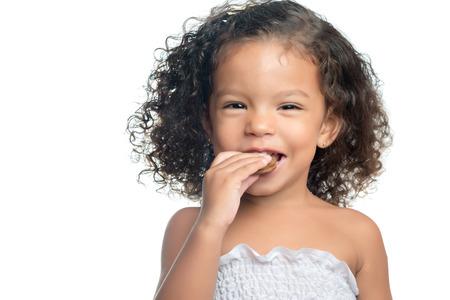 Niña alegre con un peinado afro de comer una galleta de chocolate aislado en blanco