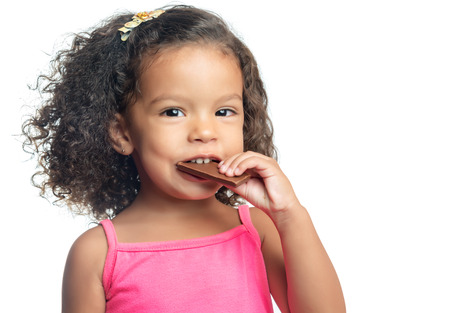 Joyful little girl with an afro hairstyle eating a chocolate bar isolated on white photo