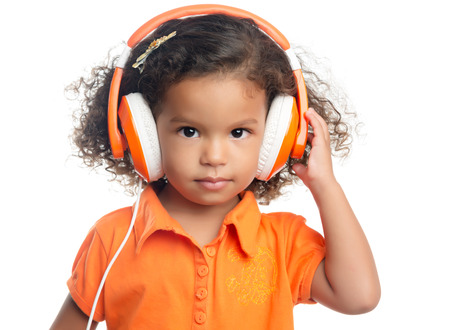 mixed race girl: Lttle girl with an afro hairstyle enjoying her music on bright orange headphones (isolated on white)