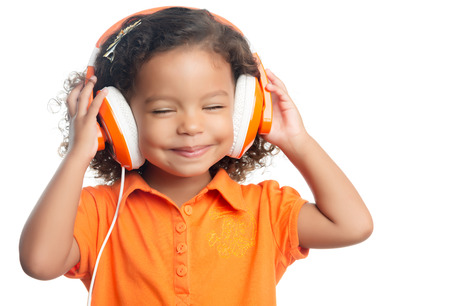 afro caribbean: Lttle girl with an afro hairstyle enjoying her music on bright orange headphones (isolated on white)