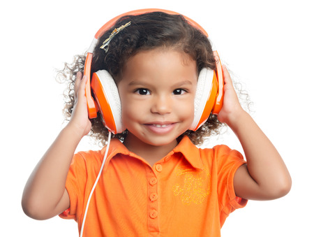 Small afro american girl with curly hair listening music on bright orange headphones photo