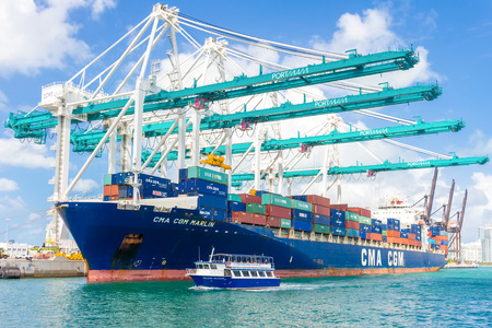 Ship with containers unloading cargo at the Port of Miami assited by big modern cranes
