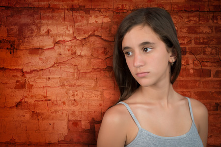 jeune fille adolescente: Triste et mélancolique adolescente s'appuyant sur un mur de briques grunge Banque d'images